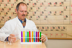 Chemist filling glass tubes with colored liquids stock photography
