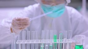 Chemist filling test tubes with green liquid stock video footage