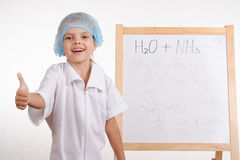 Chemist girl stands at the blackboard and shows class Royalty Free Stock Photography