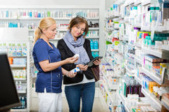 Chemist Holding Eye Drops While Customer Using Stock Photography