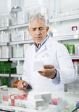 Chemist Holding Medicine At Counter In Pharmacy Stock Photos
