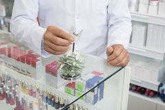 Chemist Inserting Tags In Holder At Counter In Pharmacy Royalty Free Stock Photos