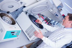 Chemist in lab coat using a centrifuge Royalty Free Stock Image