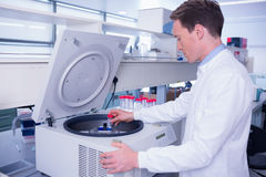 Chemist in lab coat using a centrifuge Royalty Free Stock Photography