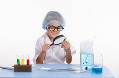 Chemist looking through a magnifying glass on powder Royalty Free Stock Image