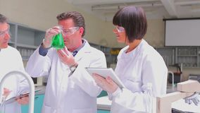 Chemist mixing green liquid in beaker with two chemists watching. In the lab stock footage