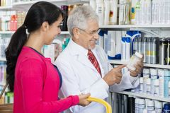 Chemist Pointing At Product While Standing By Female Customer stock photos