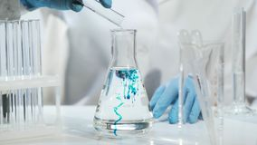 Chemist pouring substance into conical flask with liquid, chemical experiment. Stock footage Royalty Free Stock Photos