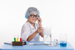 Chemist pours the blue liquid in flask Stock Images