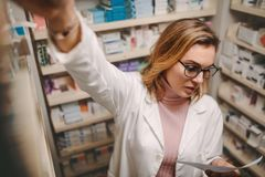 Chemist with prescription searching a medicine. Female pharmacist holding prescription searching medicine in pharmacy store. Chemist looking at prescription royalty free stock images
