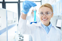 Chemist in protective eyeglasses holding test tube with reagent in lab Stock Photo