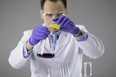 Free Chemist Researcher In Blue Gloves And Glasses Pouring Colorful Liquids In Flask Royalty Free Stock Photo - 181373825
