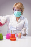 Woman in protective mask testing liquids specimen in chemical la Stock Image