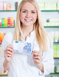 Chemist's assistant holding 20 euro Royalty Free Stock Photos