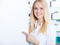 Chemist's assistant points at blank sign Stock Photo