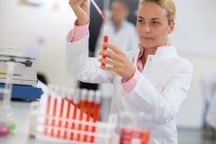 Chemist sampling liquid with pipette Stock Photo