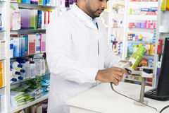 Chemist Scanning Barcode Of Product At Checkout Counter. Midsection of male chemist scanning barcode of product at checkout counter in pharmacy Stock Photo