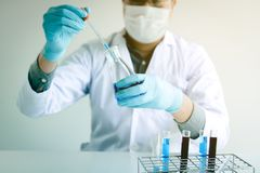 Chemist scientist conducts experiments by synthesising compounds stock photography