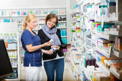 Chemist Showing Eye Drops To Customer Holding Royalty Free Stock Photography