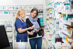 Chemist Showing Eye Drops To Customer While Royalty Free Stock Photography