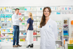 Chemist Smiling While Assistant And Customer Royalty Free Stock Photography