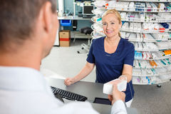 Chemist Smiling While Giving Medicine To Customer Royalty Free Stock Photos