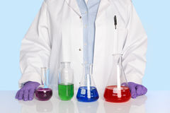 Chemist standing at a desk with chemicals Stock Image