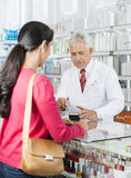 Chemist Swiping Card While Customer Standing In Pharmacy. Senior male chemist swiping credit card while customer standing in pharmacy Stock Photos