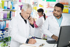 Chemist Taking Order On Phone While Colleagues Working In Pharma Royalty Free Stock Photos