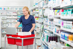 Chemist Using Laptop On Medicine Basket In Stock Photos