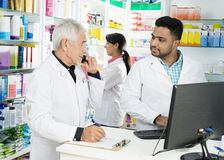 Chemist Using Phone While Looking At Colleagues Using Computer Royalty Free Stock Image