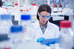 Chemist wearing safety glasses and using tablet pc Stock Images