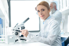 Chemist in white coat working with microscope and reagents while looking at camera in chemical laboratory. Caucasian chemist in white coat working with stock photography