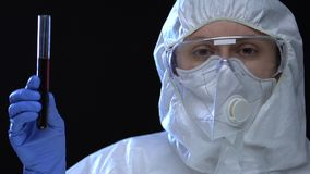 Chemist in white uniform demonstrating dangerous liquid in test-tube, viruses. Stock footage stock video footage