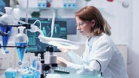 Chemist woman analysis a sample using a big magnifying glass. In the background - modern research facility with an active team stock video footage