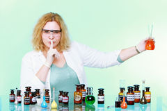 Chemist woman with glassware silence gesture isolated Stock Image