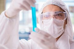 The chemist working in the laboratory with hazardous chemicals. Chemist working in the laboratory with hazardous chemicals Stock Photo