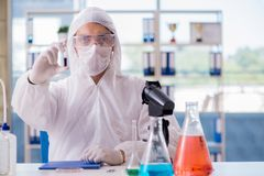 The chemist working in the laboratory with hazardous chemicals. Chemist working in the laboratory with hazardous chemicals Stock Images