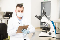 Chemist working with a microscope. Attractive young male chemist using a microscope and taking some notes of his findings in a lab Stock Images