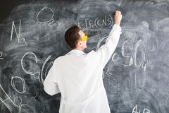 Chemist write a chemical formula on blackboard. Royalty Free Stock Image