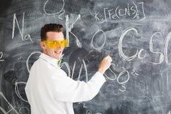 Chemist write a chemical formula on blackboard. Royalty Free Stock Photography