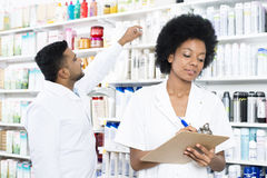 Chemist Writing On Clipboard While Colleague Arranging Products Stock Image