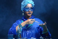 Chemistry Asian Doctor Woman with Blue Tone Fashion Make up fancy lab test dress. Studio lighting black dark background, safety gear hygiene hat and tube glass royalty free stock images