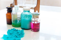 Chemistry bottles containing various substances of different colors standing on laboratory table seen over a pile of blue powder. 4 chemistry bottles containing Stock Images