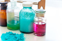 Chemistry bottles containing various substances of different colors standing on laboratory table seen over a pile of blue powder Stock Photo