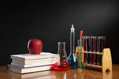 Chemistry class concept. With red apple on pile of books and chemical solution royalty free stock photos