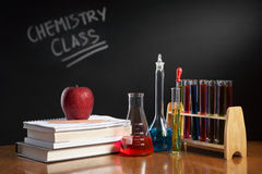 Chemistry class concept. With red apple on pile of books and chemical solution royalty free stock photography