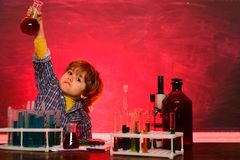A chemistry demonstration. Cheerful smiling little boy having fun against blue wall. School chemistry lessons. Preschooler. What is taught in chemistry stock images