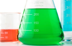 Chemistry. Closeup view showing an Erlenmeyer flask filled with green liquid in front of a small beaker with red liquid and a tall beaker with blue liquid in it stock image