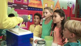 Chemistry experiment at kids party. Group of happy smiling kids watching at chemical show indoor. Science party for children stock video
